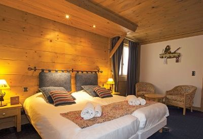 A double bed in a softly lit hotel room with wooden clad walls