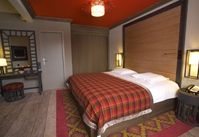 A luxury hotel room with a double bed and red tartan bedding