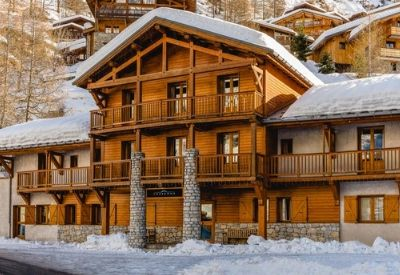 The outside of a very large wood and stone cladded ski chalet in winter
