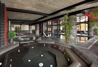 An indoor swimming pool and two hot tubs with black tiles