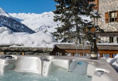 An outdoor hot tub surrounded by snow and mountains