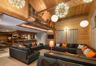 A modern, open plan living room in a ski chalet with large grey sofas