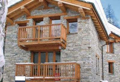 The outside of a traditional alpine building made of stone and wood