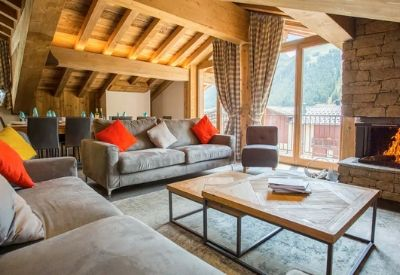 A high end chalet living room with wooden beams, sofas and an open fire