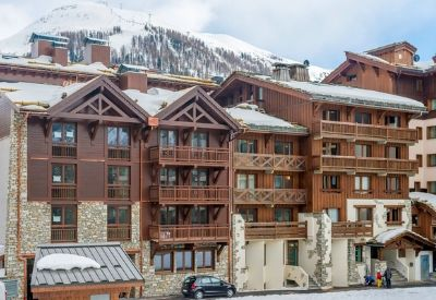 A large stone and wood hotel in front of a snow covered mountain