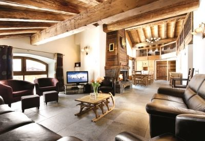 A very large ski chalet living area with leather sofas and a fire place