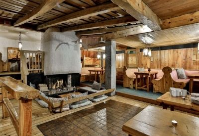 A large open plan living area in a chalet with an open fire in the centre