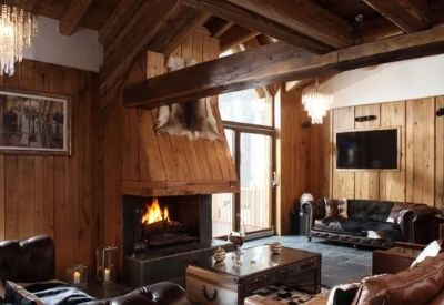 Leather sofas around a fire place with wood paneled walls