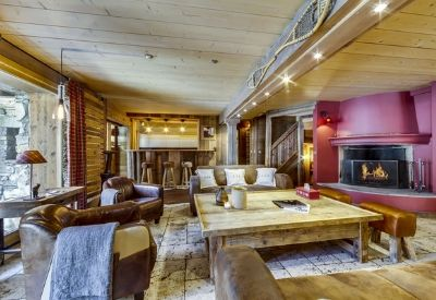 A large living area in a ski chalet with leather sofas and a fire place