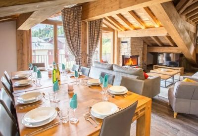A large living room and dinning area with wooden beams and an open fire place