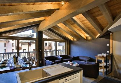 An open plan dinning room and kitchen with wooden beams