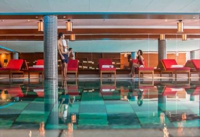 People next to an indoor swimming pool