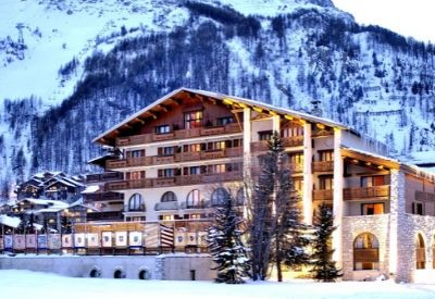 A large hotel in front of a snow covered mountain