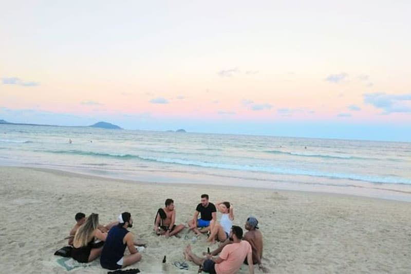 group of people or a community trip sitting around on the beach