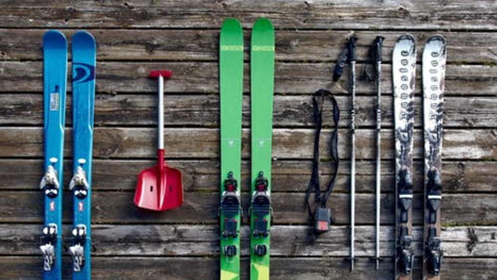 skis, poles and a shovel laid out on a table